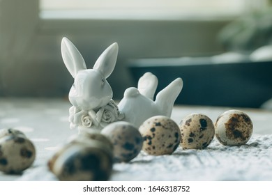 Composition of eggs on a gray background, ceramic figurine of an Easter rabbit