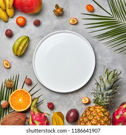 Composition from an empty white plate of green palm leaves, pineapple, mango,carambola, lychee, mandarin, and passion fruit on a gray marble table with a copy space. Flat lay