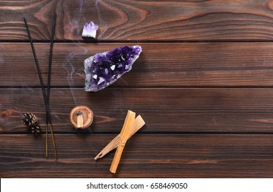 Composition of esoteric objects used for healing, meditation, relaxation and purifying. Amethyst stones, palo santo wood, Aromatic sticks on dark background.