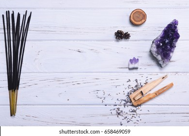 Composition of esoteric objects used for healing, meditation, relaxation and purifying. Amethyst stones, palo santo wood, Aromatic sticks on white background.