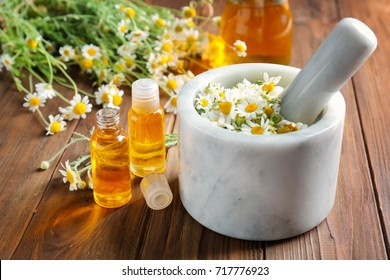Composition with essential oil and chamomile flowers on wooden table