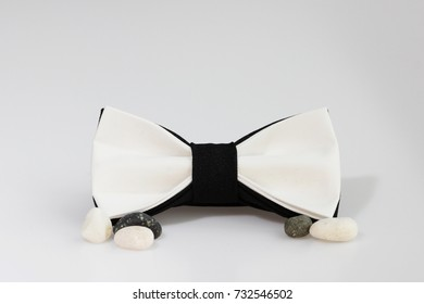 Composition: Extravagant black and white bow tie and sea pebbles on a white background.