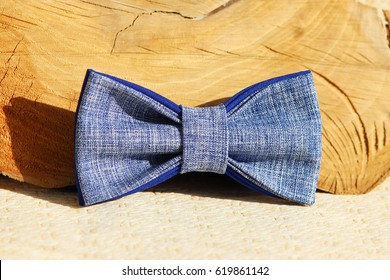 Composition: Extravagant blue bow tie and wooden stick curve on a beige background.
