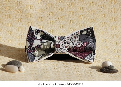 Composition: Extravagant bow tie and pebbles on a beige background.