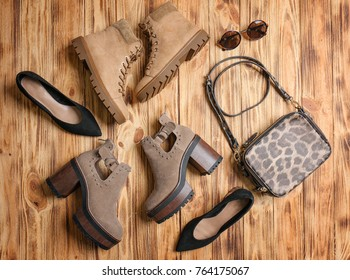 Composition with female stylish shoes and bag on wooden background