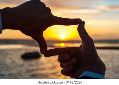 Composition finger frame- man's hands capture the sunset. Multicolored horizontal outdoors image.