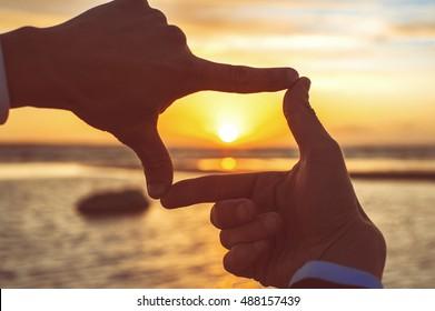 Komposition Fingerrahmen - die Hände des Mannes fangen den Sonnenuntergang auf dem Hintergrund beleuchtet. mehrfarbiges horizontales Außenbild mit Vintage-Filter