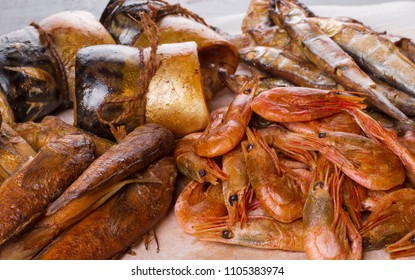 composition of fish background closeup. smoked seafood fish and shrimp. herring, perch, capelin, mackerel home smoking. fish background closeup