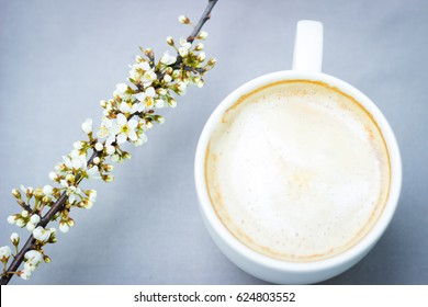 Composition with flowers and a coffee cup on white background. Flat lay, top view. Feminine background