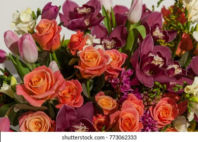 composition of flowers from pink roses, burgundy orchids, red tulips, hyacinth and hrzemtem. Flower Arrangement in a box for a girl of roses, tulips and orchids on a white background