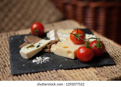 Composition with french cheese served with fresh ripe tomatoes and bread. Served on a rustic basket to create a picnic mood