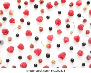 Composition of fresh berries: raspberry, strawberry, black currant on a white background. Food pattern background. Healthy food concept. Top view, flat lay.