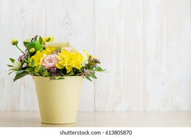 Composition of fresh flowers in a bucket on a wooden background. Copyspace