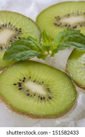 Composition of fresh green kiwi fruit slices with ice cubes and mint herb leaf.