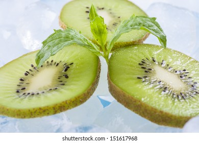 Composition of fresh green kiwi fruit slices with ice cubes and mint herb leafs.