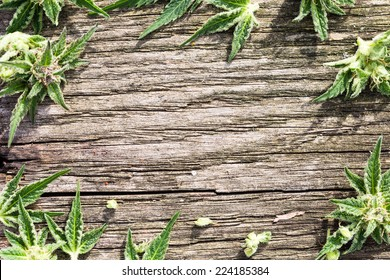 Composition of fresh marijuana plant bud with crystals and leaves on grunge wooden desk. View from above. Copy space.