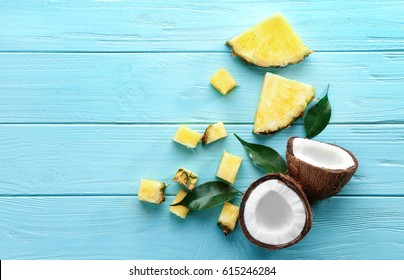 Composition of fresh pineapple slices and coconut on color wooden background