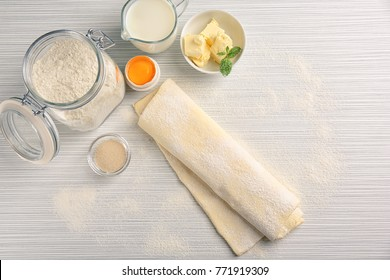 Composition with fresh raw puff dough on table