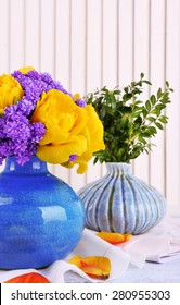 Composition with fresh spring flowers in ceramics vases on wooden background