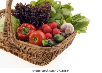 Composition with fresh vegetables in the basket  isolated on white background