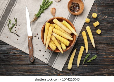 Composition with fresh young baby corn on wooden background
