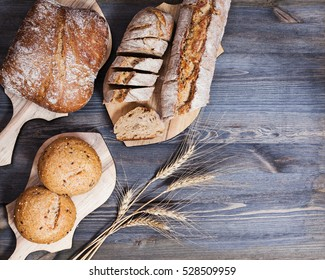 Composition of freshly baked bread on chopping boards and wheat ears on dark wooden background. Bakery and healthy eating. Flat lay. Top view