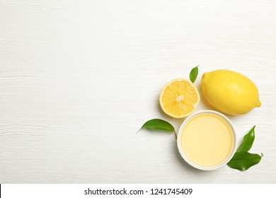 Composition with freshly squeezed lemon juice and space for text on white wooden background
