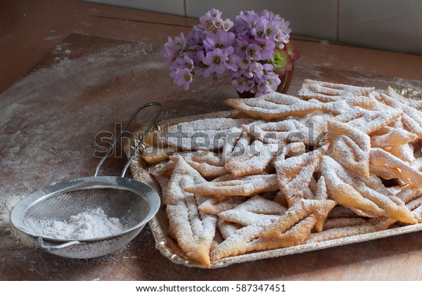 composition with fried biscuits period of Italian carnivals on a tray, a sieve to sift the sugar and pink flowers on a wooden table. Angel wings, chiacchiere