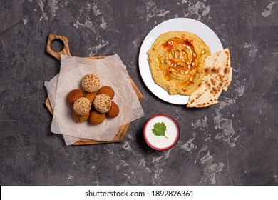 Composition of fried falafel on a kitchen board, hummus on a pla