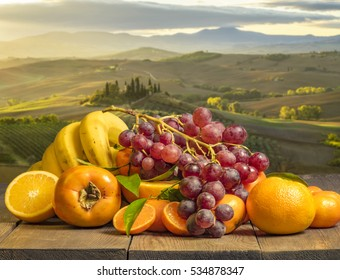 composition of fruits on wooden table on background Tuscan countryside