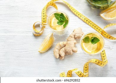 Composition with ginger tea and measuring tape on wooden table. Weight loss concept