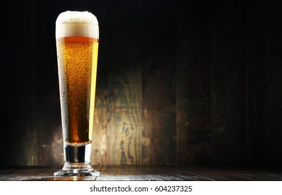 Composition with glass of beer on wooden background.