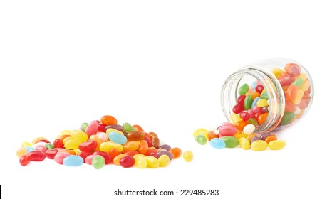 Composition of a glass jar and multiple colorful jelly bean candies, isolated over the white background