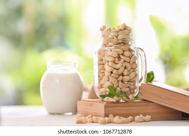 Composition with glass jar of tasty cashew nuts on table against blurred background