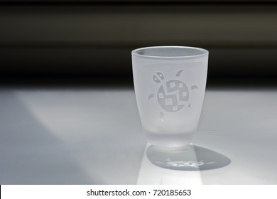 Composition with glass of liquor in the back light, decorated with turtle design