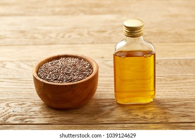 Composition of glass oil jars, wooden bowl and scoop with flax seeds, selective focus