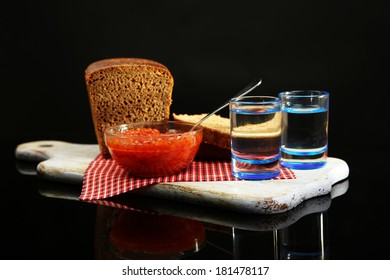 Composition with glasses of vodka, red caviar, fresh bread on wooden board,  isolated on black