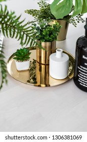 Composition of gold mirror vase and white ceramic pot with artificial plant setting on gold mirror plate on natural wood table top / object isolation / interior design decoration