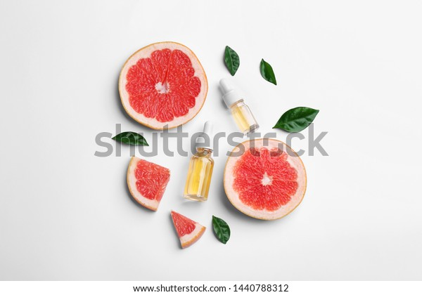 Composition with grapefruit slices and bottles of essential oil on white background, top view