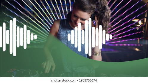 Composition of green curve and white sound level meter over smiling female dj and colourful lights. audio sound visualisation concept digitally generated image.