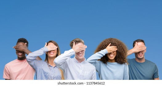 Composition of group of friends over blue blackground smiling and laughing with hand on face covering eyes for surprise. Blind concept.