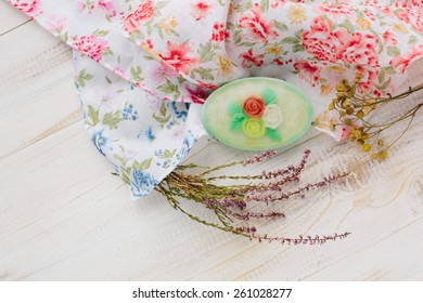 Composition with handmade oval floral soap roses, colored fabrics and branches of dry lavender, lying on a white wooden background
