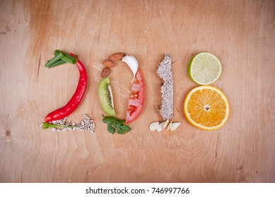 A composition of healthy food fruit, vegetables, brown bread, seeds and herbs which make 2018 number.