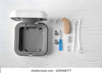 Composition with hearing aid and accessories on light background
