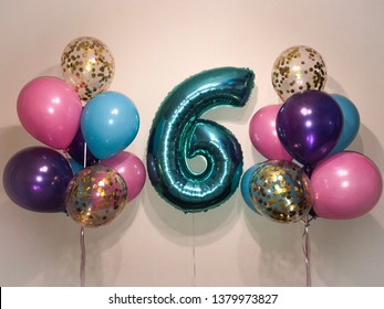 Composition of helium balloons purple, blue, pink,balloons with gold confetti as well as a large figure of six tiffany color