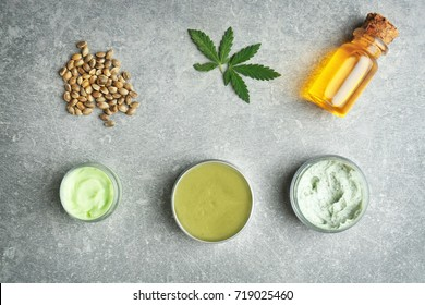 Composition with hemp cosmetic products and natural ingredients on grey background