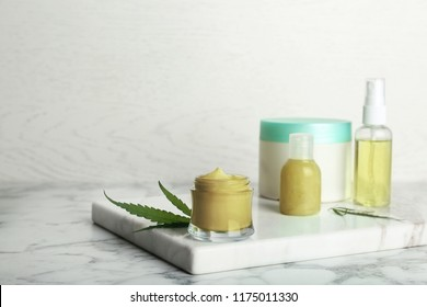 Composition with hemp lotion on marble table. Space for text