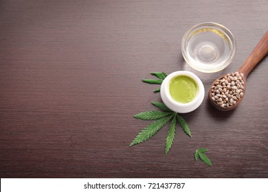 Composition with hemp lotion, seeds and oil on wooden background