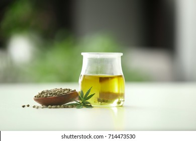 Composition with hemp oil and seeds on blurred background