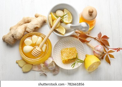 Composition with honey and garlic as natural cold remedies on white wooden background, top view